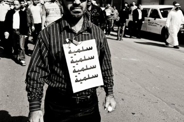 """Διαδηλωτής στην κηδεία του Ali Mushaima, τον Φεβρουάριο του 2011. Η ταμπέλα γράφει """"Ειρήνη"""" (φωτο Saeed Saif)"""