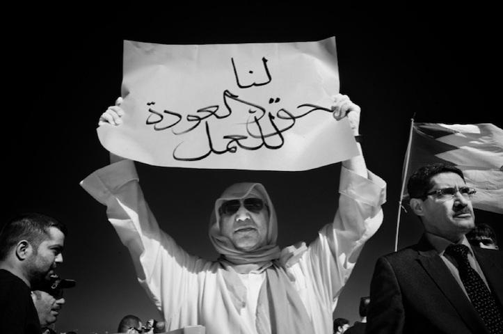 """Το χαρτόνι του διαδηλωτή γράφει: """"Έχουμε το δικαίωμα να επιστρέψουμε στις δουλειές μας"""", σε διαμαρτυρία έξω από το Υπουργείο εργασίας, στην Isa Town, το Νοέμβριο του 2011. Πολλοί εργαζόμενοι απολύθηκαν από την κυβέρνηση όταν ξεκίνησαν οι διαμαρτυρίες (φωτο Saeed Saif)."""
