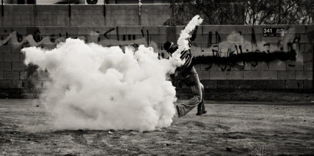 Διαδηλωτής πετάει δακρυγόνο πίσω στην αστυνομία στην Σίτρα, τον Δεκέμβριο 2011 (φωτο Saeed Saif)