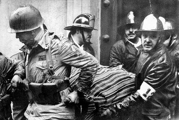 Στρατιώτες και πυροσβέστες μεταφέρουν το σώμα του Αουγκούστο Πινοσέτ, μετά τον βοβμβαρδισμό του προεδρικού μεγάρου, στο πραξικόπημα της 11/9.1973 από τον Πινοσέτ